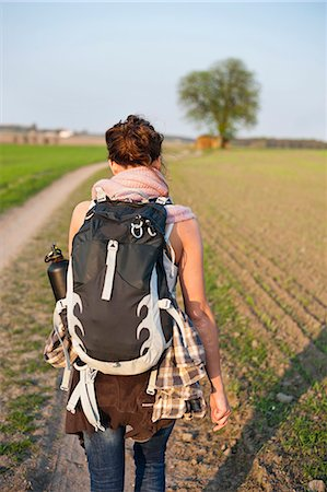 Rear view of young woman with backpack on hiking trail Stock Photo - Premium Royalty-Free, Code: 698-06615638