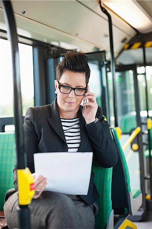 Mid adult businesswoman with document using cell phone in bus Stock Photo - Premium Royalty-Free, Code: 698-06615646