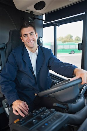 Portrait of happy mid adult male bus driver at steering wheel Stock Photo - Premium Royalty-Free, Code: 698-06615650
