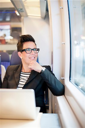 Thoughtful mid adult businesswoman with laptop looking out from train window Stock Photo - Premium Royalty-Free, Code: 698-06615664