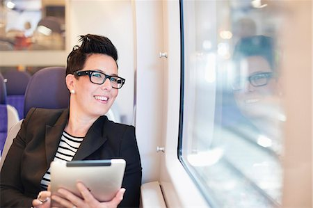 Happy mid adult businesswoman with digital tablet looking out from train window Stock Photo - Premium Royalty-Free, Code: 698-06615665