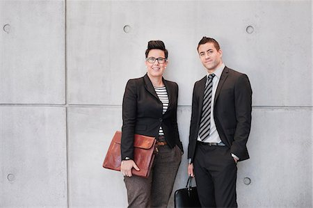 Portrait of happy business people holding bags against wall Stock Photo - Premium Royalty-Free, Code: 698-06615669