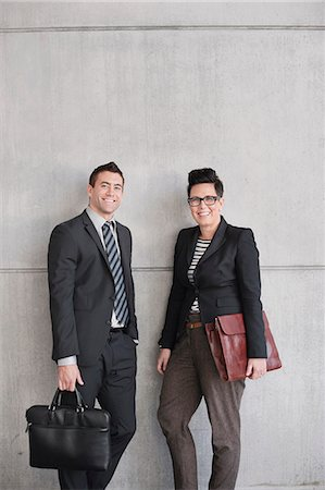 Portrait of happy business people with bags standing against wall Stock Photo - Premium Royalty-Free, Code: 698-06615670