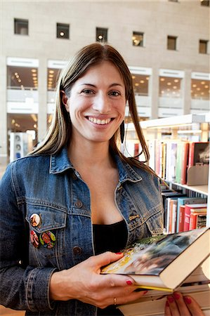 Portrait of woman with stack of books in library Stock Photo - Premium Royalty-Free, Code: 698-06615747