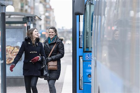 Happy friends in jackets walking by bus Stock Photo - Premium Royalty-Free, Code: 698-06615845