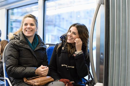 Happy female friends looking away while sitting in bus Stock Photo - Premium Royalty-Free, Code: 698-06615848