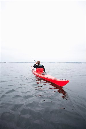 Rear view of mid adult man kayaking in river Stock Photo - Premium Royalty-Free, Code: 698-06615875