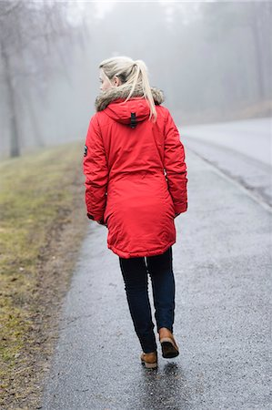 Rear view of young woman in winter coat walking on road Stock Photo - Premium Royalty-Free, Code: 698-06615894