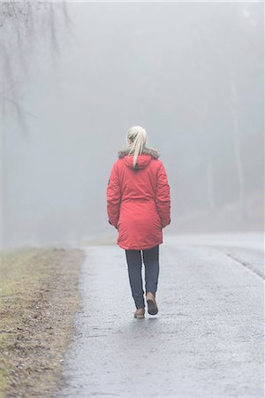 Rear view of young woman walking on road in a foggy day Stock Photo - Premium Royalty-Free, Code: 698-06615895