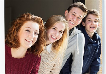 Portrait of happy young friends looking through house window Stock Photo - Premium Royalty-Free, Code: 698-06615915