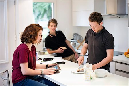 Young girl using digital tablet with male friends standing at kitchen counter Stock Photo - Premium Royalty-Free, Code: 698-06615949