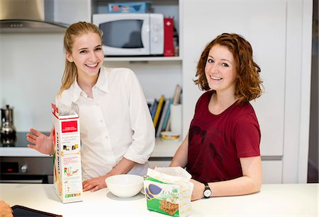 Portrait of happy female friends standing together at kitchen counter Stock Photo - Premium Royalty-Free, Code: 698-06615951