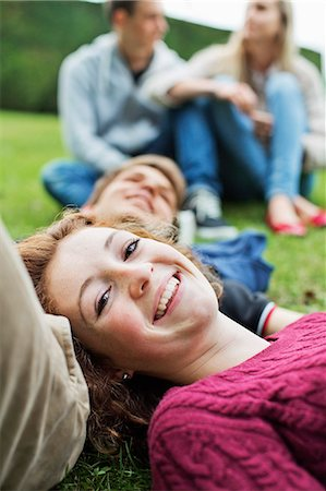 four - Portrait of happy young girl with head on boy's stomach and couple sitting in background at park Stock Photo - Premium Royalty-Free, Code: 698-06615975