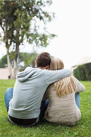 Rear view of young couple with arms around sitting at park Stock Photo - Premium Royalty-Free, Code: 698-06615976