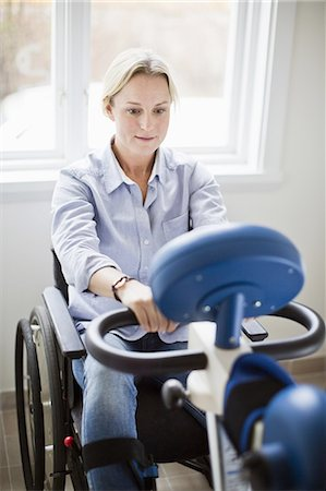 disable exercising - Disabled mid adult woman using motomed bike Stock Photo - Premium Royalty-Free, Code: 698-06616006