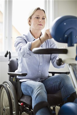 disable exercising - Disabled woman in wheelchair using motomed bike Stock Photo - Premium Royalty-Free, Code: 698-06616007