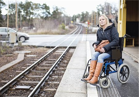 Disabled woman in wheelchair waiting for the train at railway station Stock Photo - Premium Royalty-Free, Code: 698-06616008