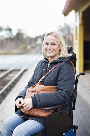 Portrait of happy disabled woman in wheelchair at railway station platform Stock Photo - Premium Royalty-Free, Code: 698-06616009