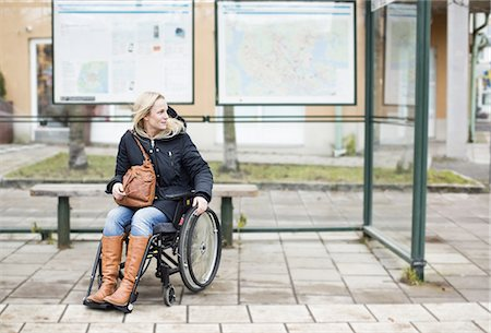 Disabled woman in wheelchair waiting at bus stop Stock Photo - Premium Royalty-Free, Code: 698-06616010