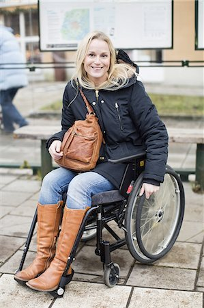 Portrait of happy disabled woman in wheelchair at bus stop Stock Photo - Premium Royalty-Free, Code: 698-06616011