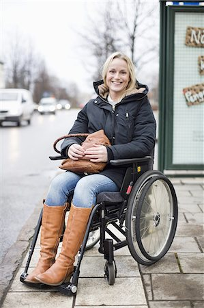 Portrait of happy disabled woman in wheelchair smiling outdoors Stock Photo - Premium Royalty-Free, Code: 698-06616013