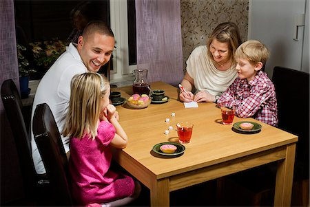 Happy family playing dice game at home Stock Photo - Premium Royalty-Free, Code: 698-06616024