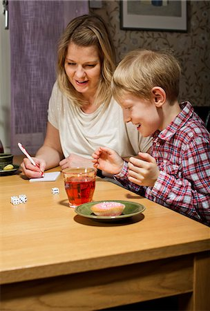 Excited boy playing dice game while mother writing scores at table Stock Photo - Premium Royalty-Free, Code: 698-06616025