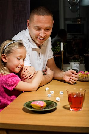 Father and daughter playing with dice game at table Stock Photo - Premium Royalty-Free, Code: 698-06616026