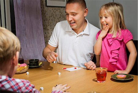 Father with children playing dice game at table Stock Photo - Premium Royalty-Free, Code: 698-06616027