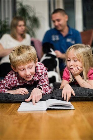 Siblings reading book while lying on front with parents in background Stock Photo - Premium Royalty-Free, Code: 698-06616036