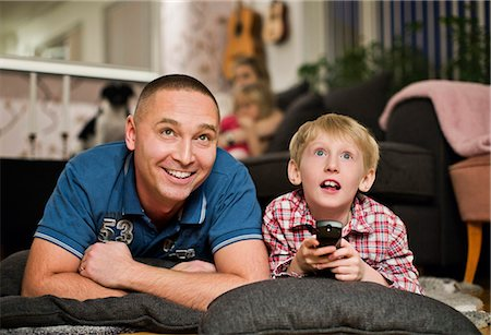 Surprised little boy watching TV with father at home Stock Photo - Premium Royalty-Free, Code: 698-06616030