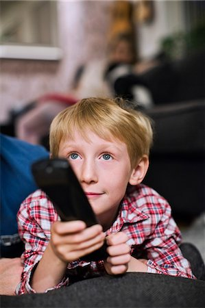 Little boy with remote control watching TV at home Stock Photo - Premium Royalty-Free, Code: 698-06616031