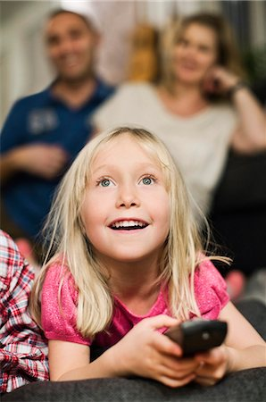 Little girl with remote control watching TV and parents sitting in background Stock Photo - Premium Royalty-Free, Code: 698-06616033
