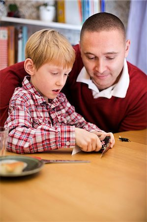 Boy making craft at table while father looking at him Stock Photo - Premium Royalty-Free, Code: 698-06616043