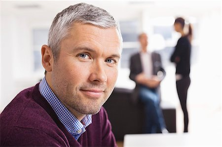 Portrait of mature businessman smiling with colleagues in the background Stock Photo - Premium Royalty-Free, Code: 698-06616064