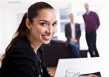 Portrait of happy business woman with colleagues in the background Stock Photo - Premium Royalty-Free, Code: 698-06616065