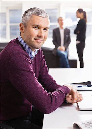 Portrait of businessman smiling at desk with colleagues in the background Stock Photo - Premium Royalty-Free, Code: 698-06616063