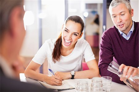 Happy business people in a meeting at desk Stock Photo - Premium Royalty-Free, Code: 698-06616089