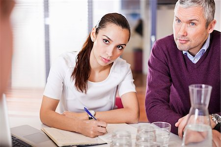 Businesswoman taking notes while sitting with colleagues in a meeting Stock Photo - Premium Royalty-Free, Code: 698-06616090