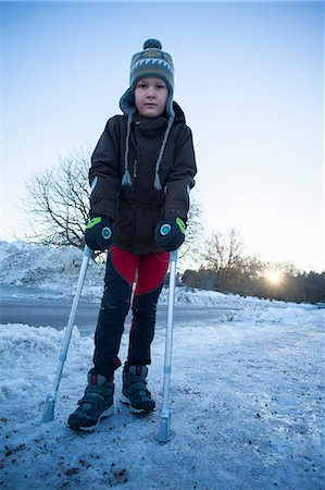 Portrait of disabled boy in warm clothing standing on snowy landscape Stock Photo - Premium Royalty-Free, Code: 698-06616122