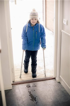 Portrait of disabled girl with crutches entering house Stock Photo - Premium Royalty-Free, Code: 698-06616143