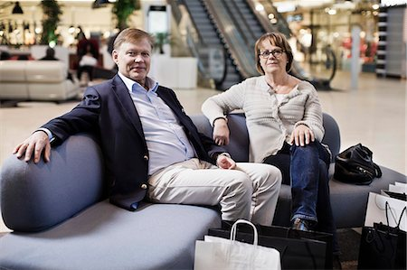 Portrait of senior couple with shopping bags sitting on sofa at mall Stock Photo - Premium Royalty-Free, Code: 698-06616185