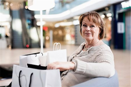 Happy senior woman with shopping bags sitting on sofa at mall Stock Photo - Premium Royalty-Free, Code: 698-06616195