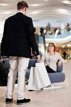shopping mall - Rear view of senior man carrying shopping bags with woman on sofa at mall Stock Photo - Premium Royalty-Free, Code: 698-06616197