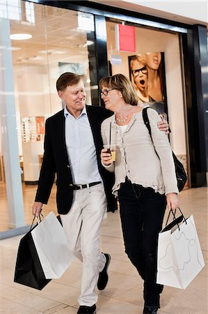 people on mall - Happy senior couple with shopping bags walking by store in mall Stock Photo - Premium Royalty-Free, Code: 698-06616199
