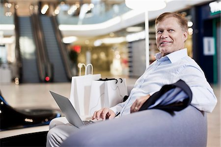 shopping mall - Happy senior man sitting on sofa with laptop at shopping mall Stock Photo - Premium Royalty-Free, Code: 698-06616191