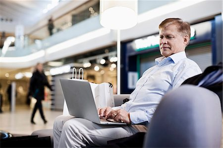 shopping mall - Senior man on sofa using laptop at shopping mall Stock Photo - Premium Royalty-Free, Code: 698-06616192