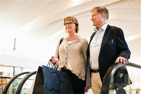 shopping mall - Happy senior couple with bags on an escalator in shopping mall Stock Photo - Premium Royalty-Free, Code: 698-06616207