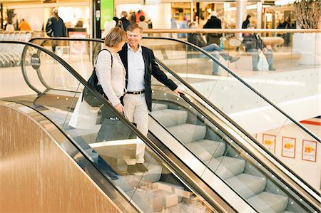 shopping mall - Happy senior couple on an escalator in shopping mall Stock Photo - Premium Royalty-Free, Code: 698-06616208