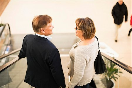 Rear view of senior couple on an escalator in shopping mall Stock Photo - Premium Royalty-Free, Code: 698-06616209